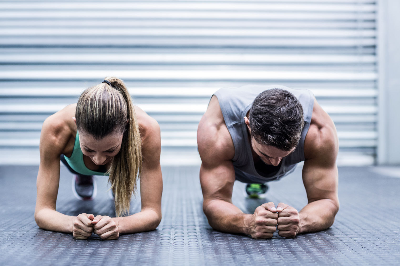 42329549 - front view of a muscular couple doing planking exercises